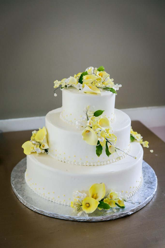 Wedding cake with yellow flowers at Highlands Country Club wedding ceremony