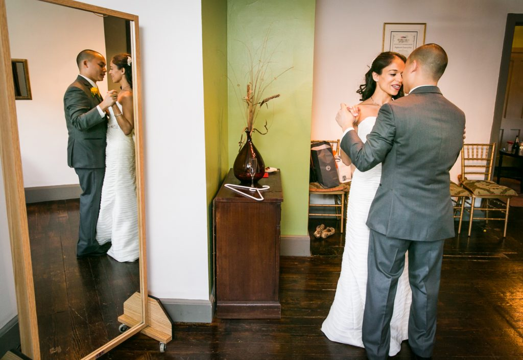 Bride and groom dancing in bridal suite and reflection in mirror