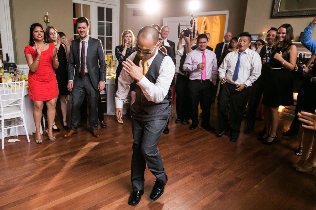 Groom doing robot dance in front of guests