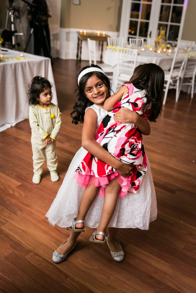 Flower girl lifting up little girl with baby in background