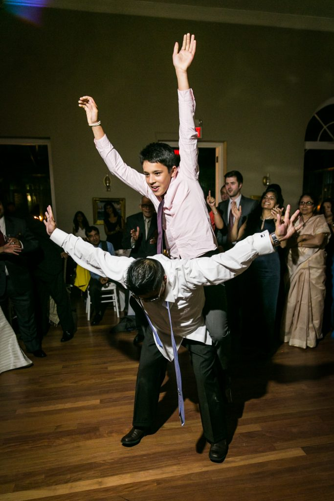 Two guests dancing wildly with arms raised