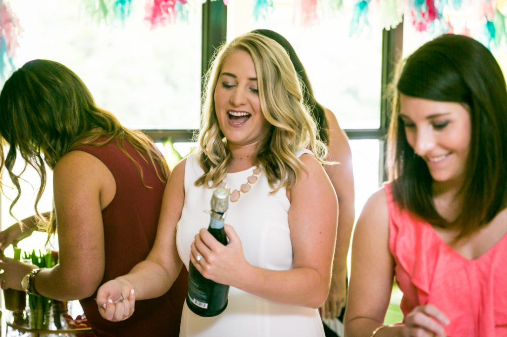 Bride-to-be opening bottle of champagne at a Florida bridal shower