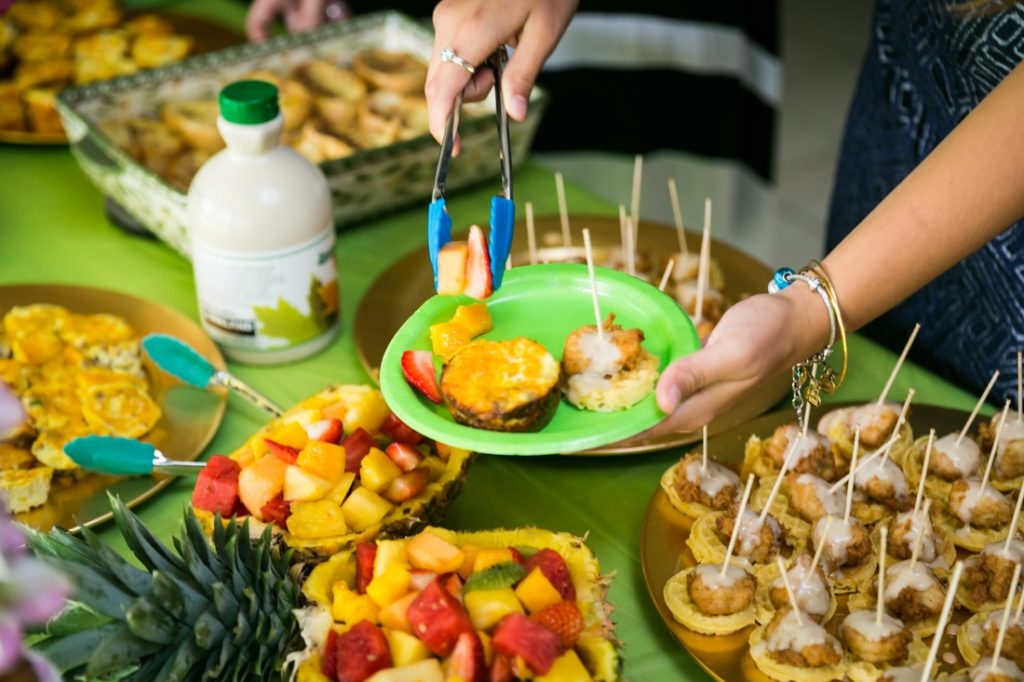 Hands putting food on a green plate at a Florida bridal shower
