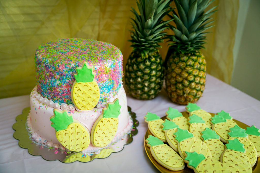 Cake decorated with pineapple cookies and two real pineapples