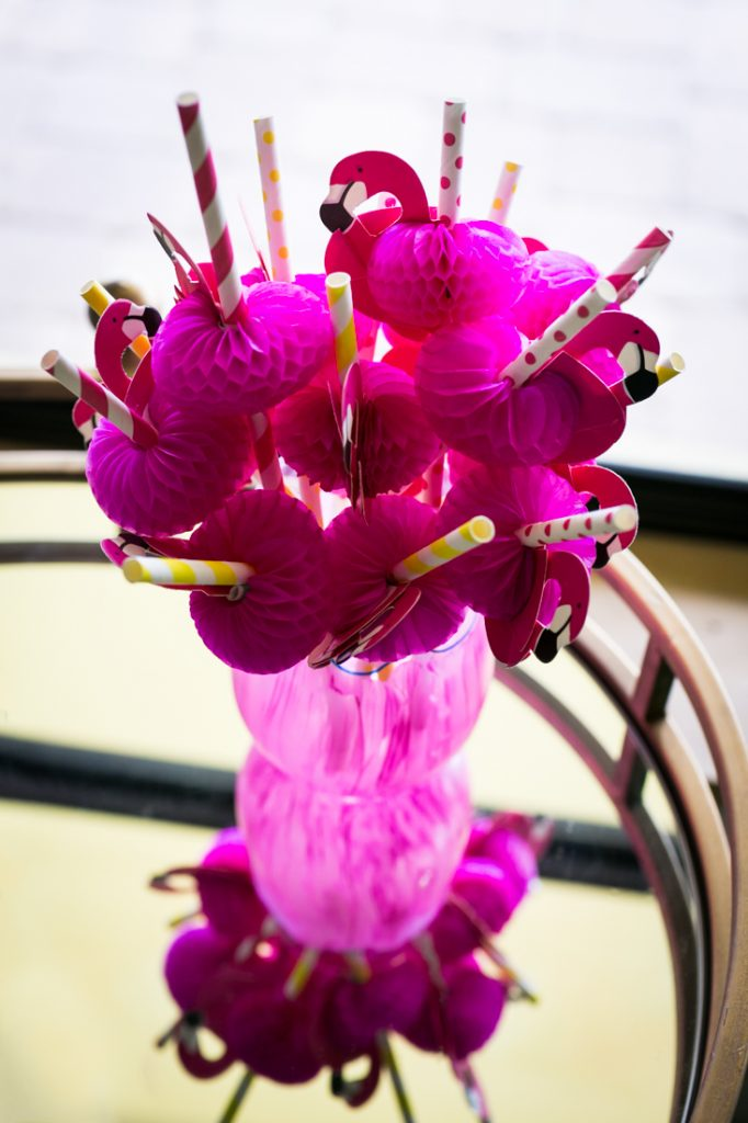 Pink glass filled with straws shaped like flamingoes