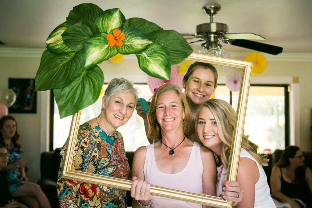 Guests looking through gold frame decorated with leaves