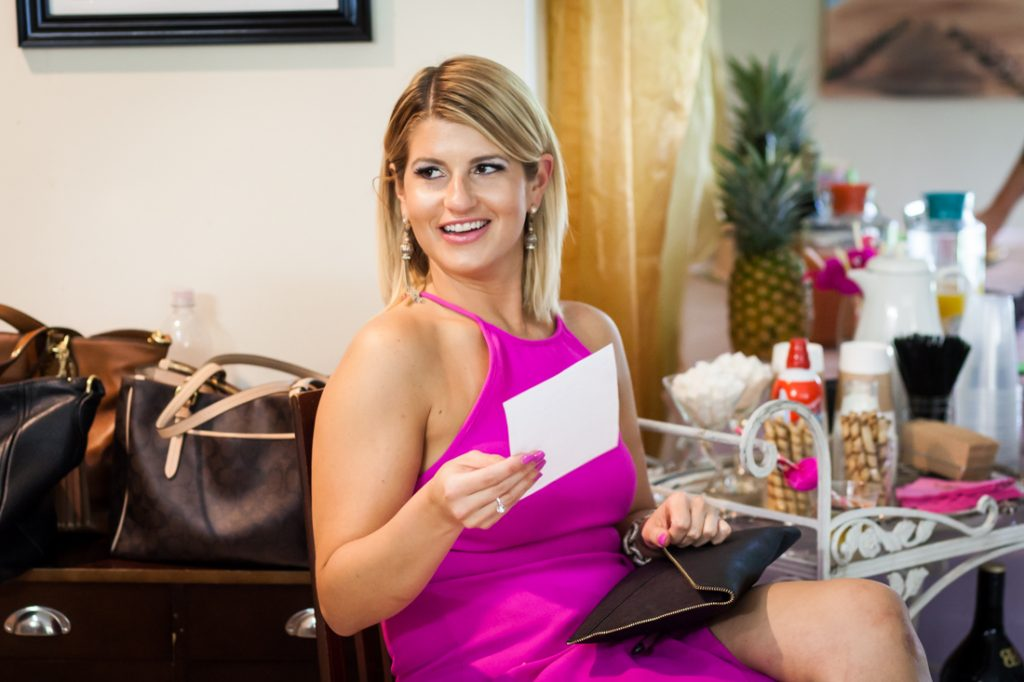 Female guest wearing pink dress and holding card at a Florida bridal shower