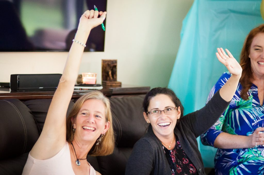 Two female guests with hands raised during Florida bridal shower