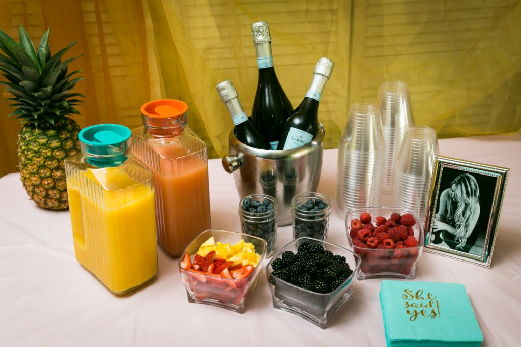 Champagne bar with glasses, fruit, and bottles