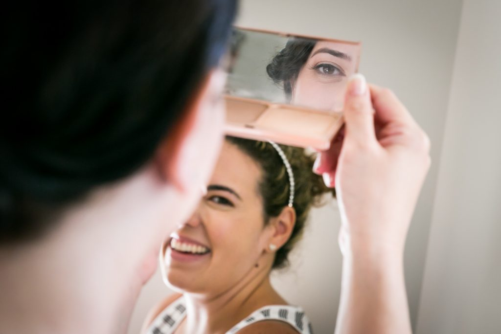Bridesmaid laughing and bride reflected in mirror