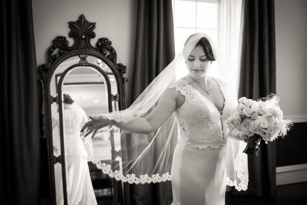 Black and white photo of bride playing with veil