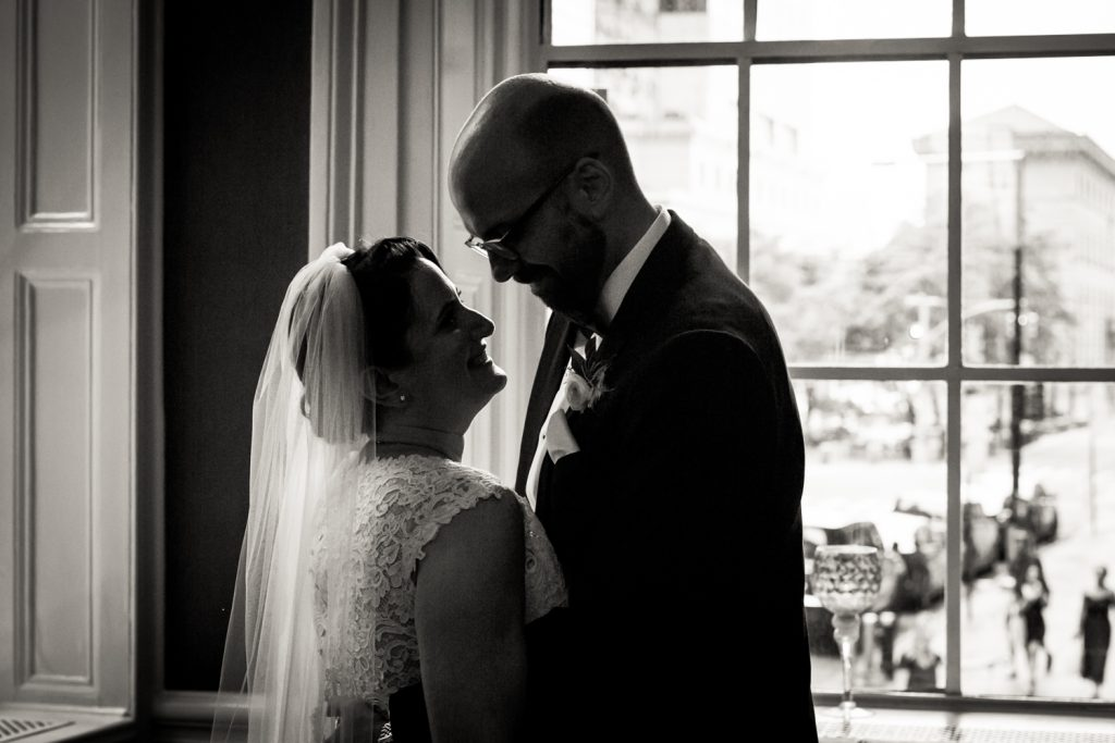 Black and white photo of backlit bride and groom