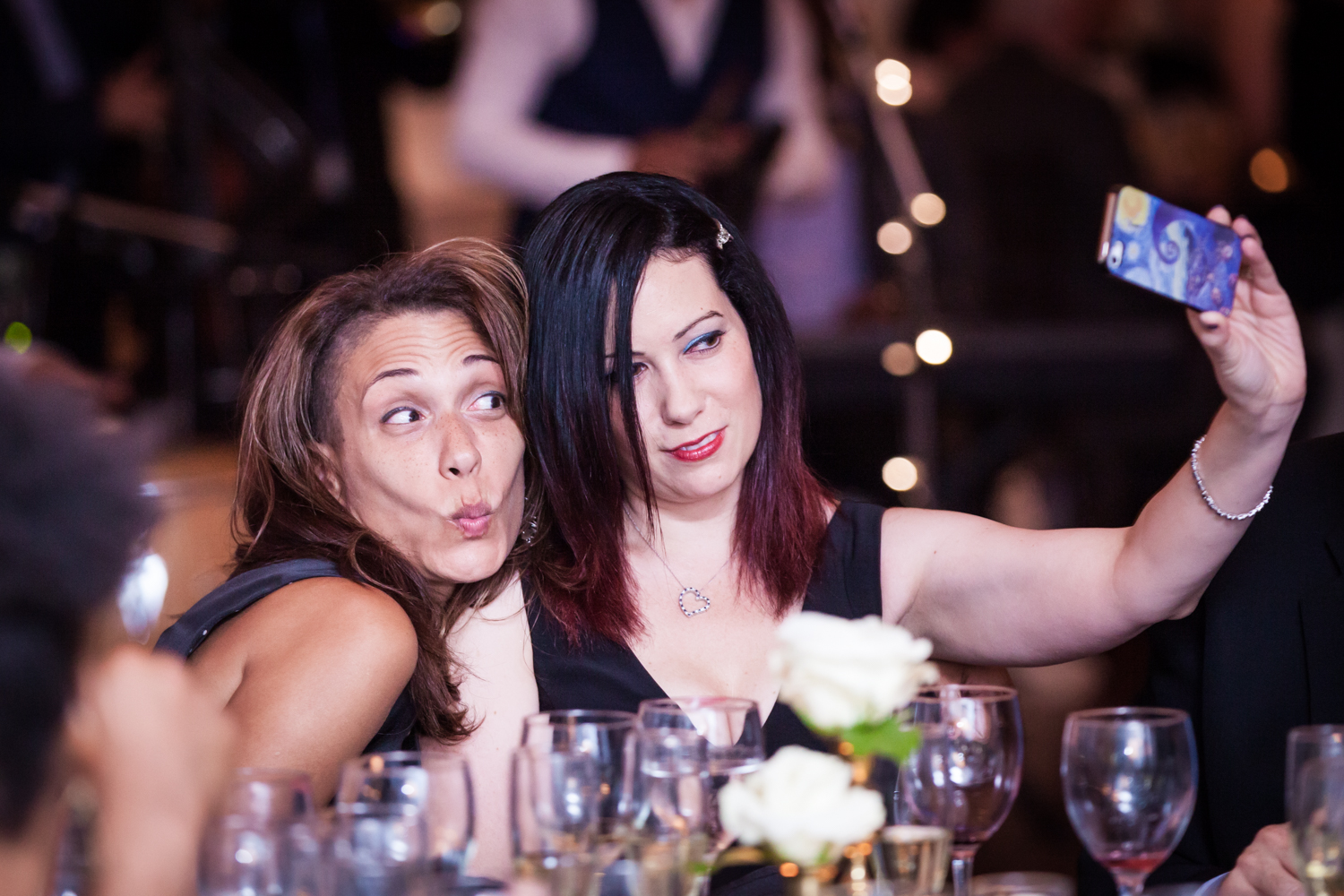India House wedding photos of two female guests taking a selfie at a table