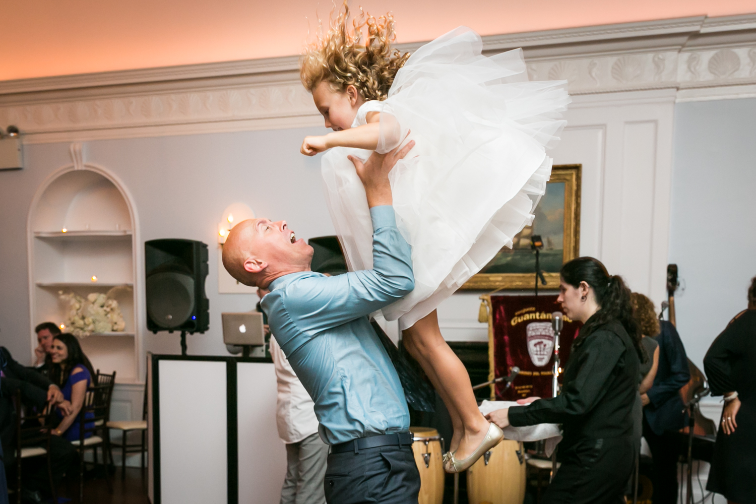 Man throwing little girl up in the air at wedding reception