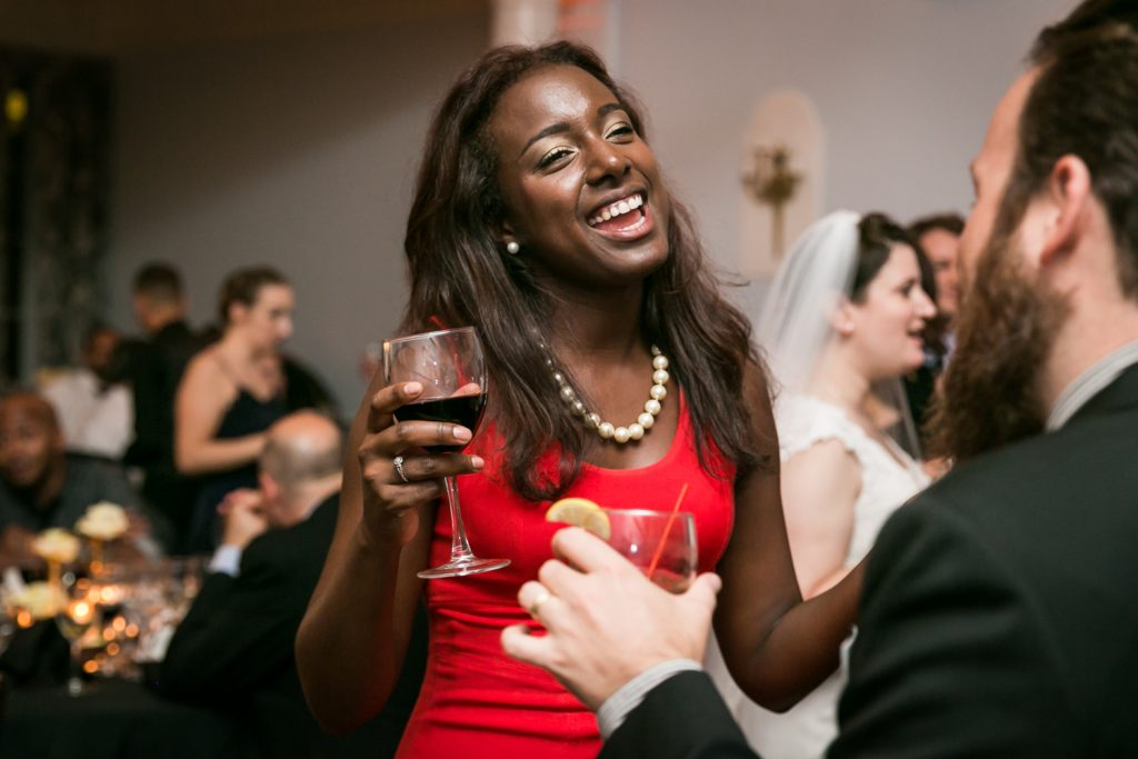 African American woman wearing red dress dancing at India House wedding