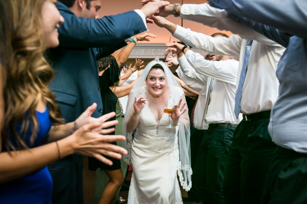 Bride going under arch of guest arms at India House wedding