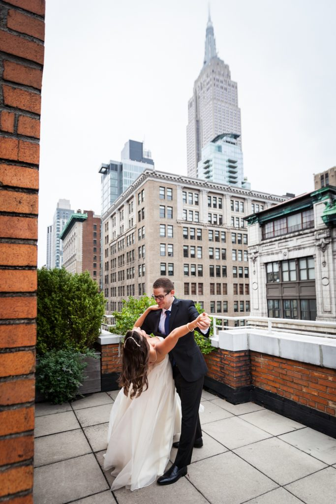 Bride and groom dancing on terrace with Empire State Building in background