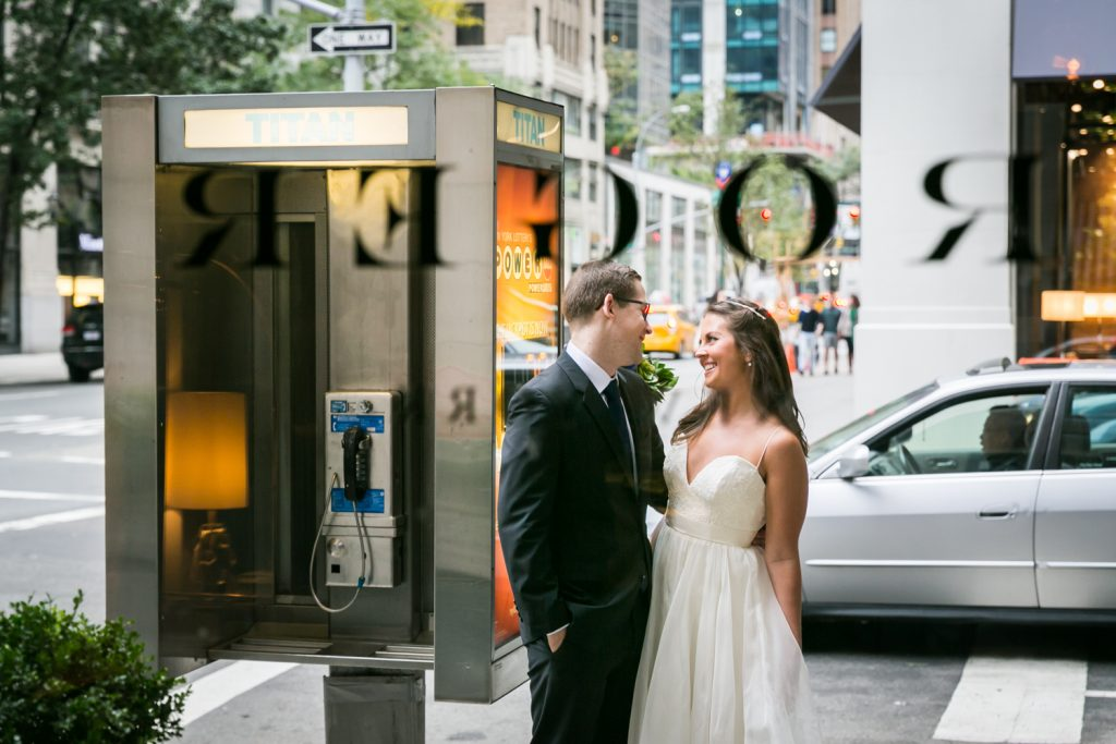 View of bride and bridegroom beside a phone booth