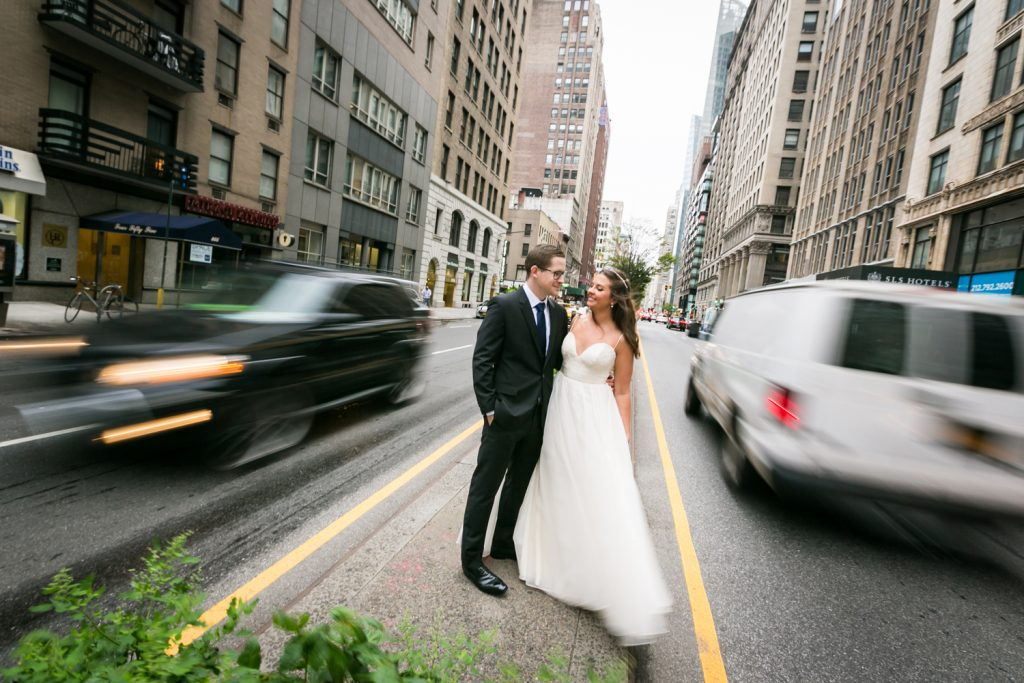 Bride and groom in focus with cars zooming by out of focus