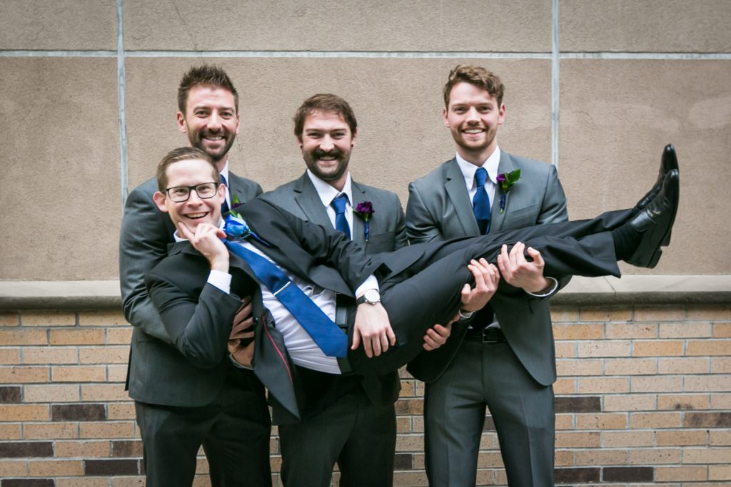 Portrait of groomsmen holding up groom