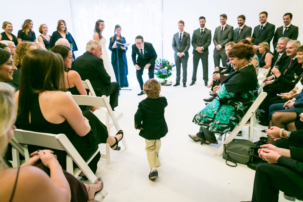 Ring bearer running towards groom during Bathhouse Studios wedding ceremony