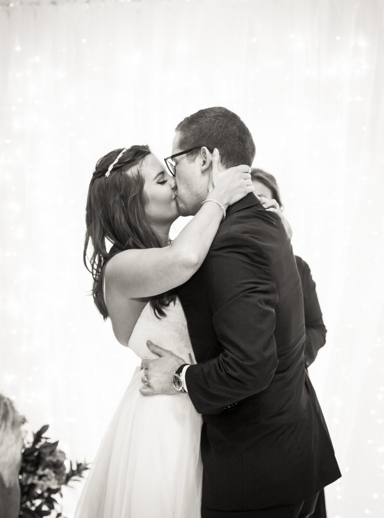 Black and white photo of bride and groom kissing after Bathhouse Studios wedding ceremony
