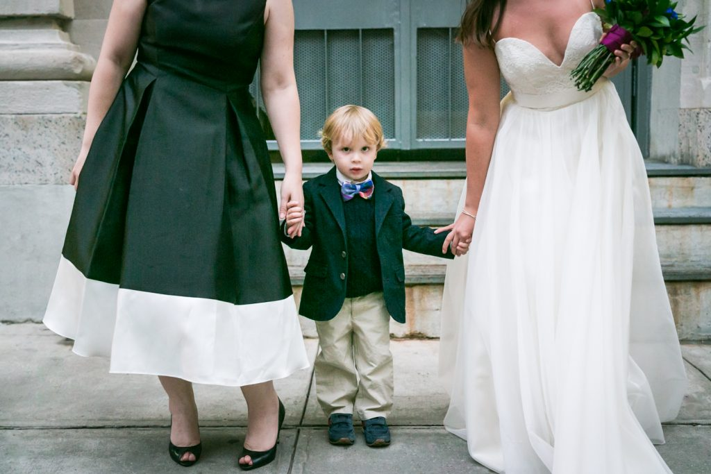 Close up photo of little boy holding hands of two women