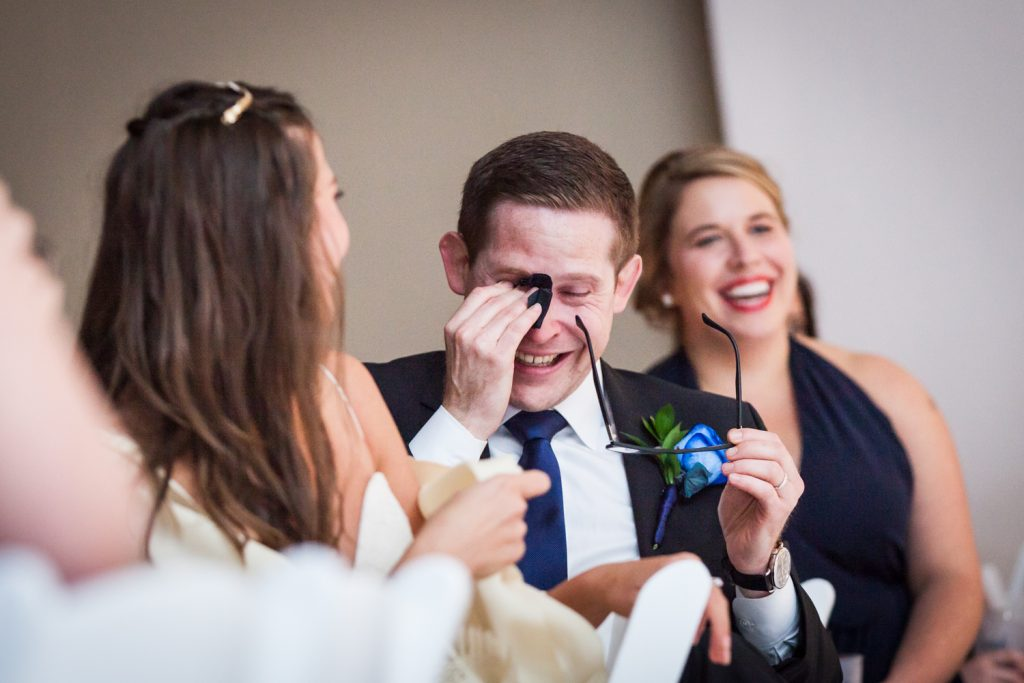 Groom wiping away tears of laughter