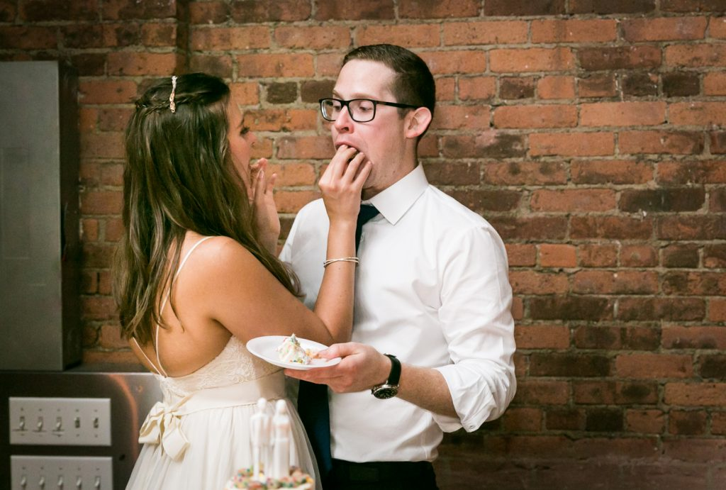 Bride feeding wedding cake to groom at Bathhouse Studios wedding