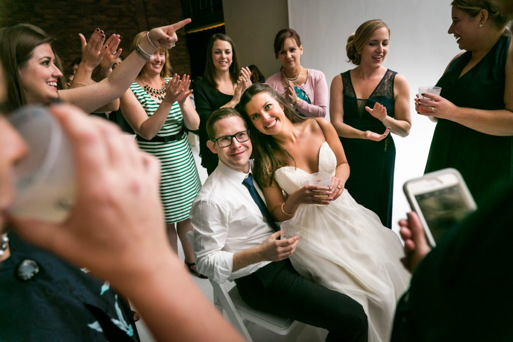 Bride and groom sitting in circle of guests at Bathhouse Studios wedding