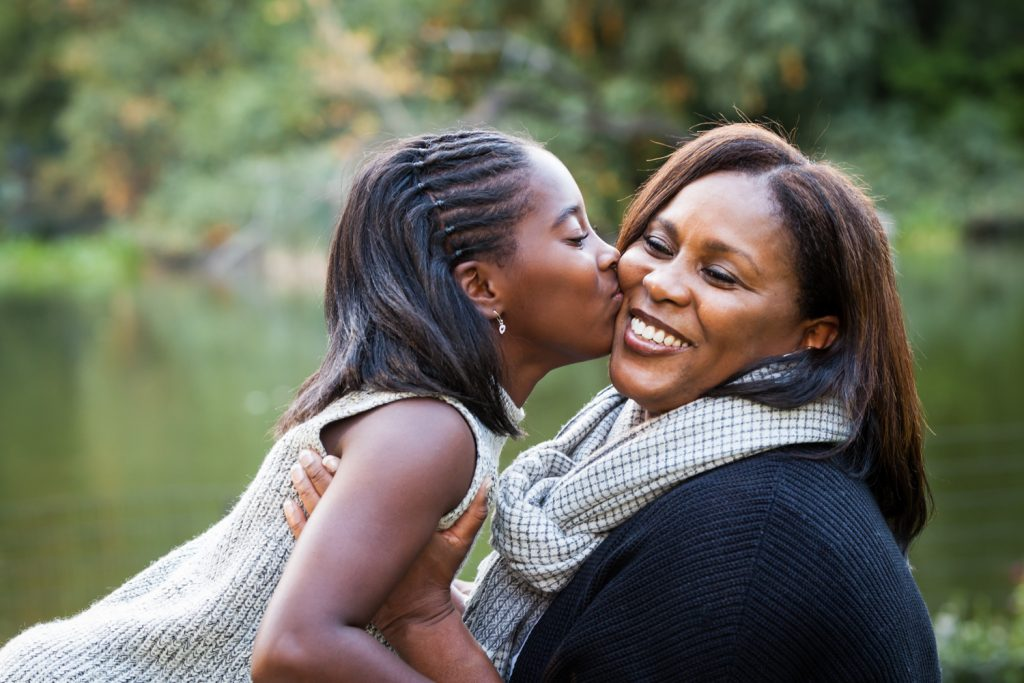 Central Park fall family portrait of daughter kissing mother's cheek