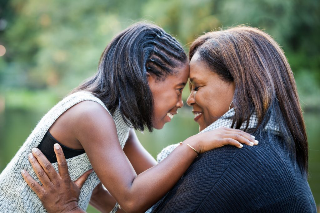 Central Park fall family portrait of mother and daughter touching foreheads