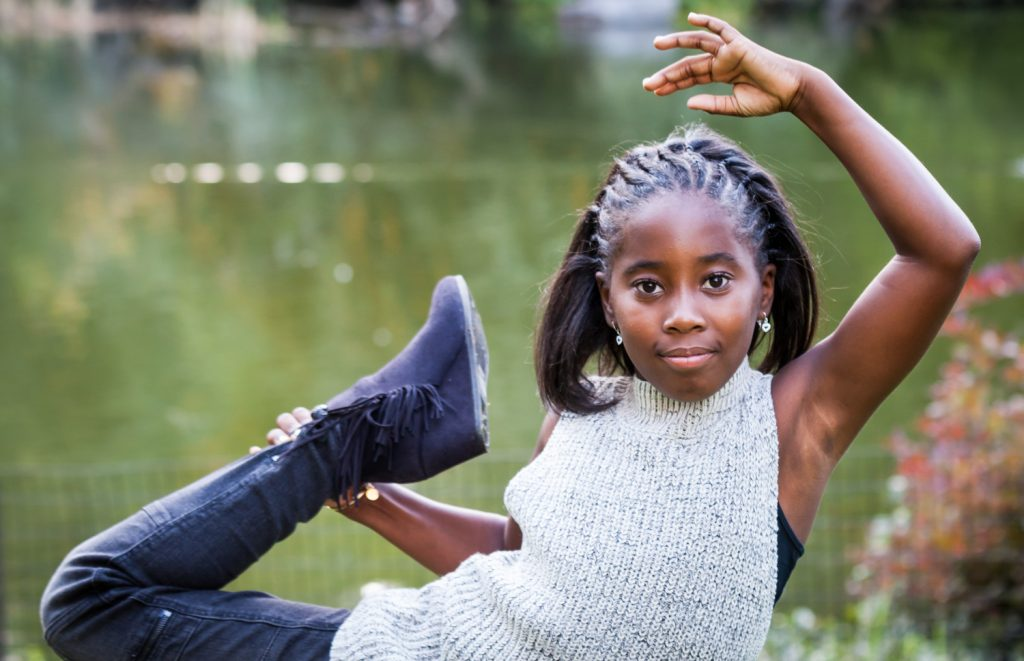 Young girl wearing sleeveless sweater doing gymnastics pose