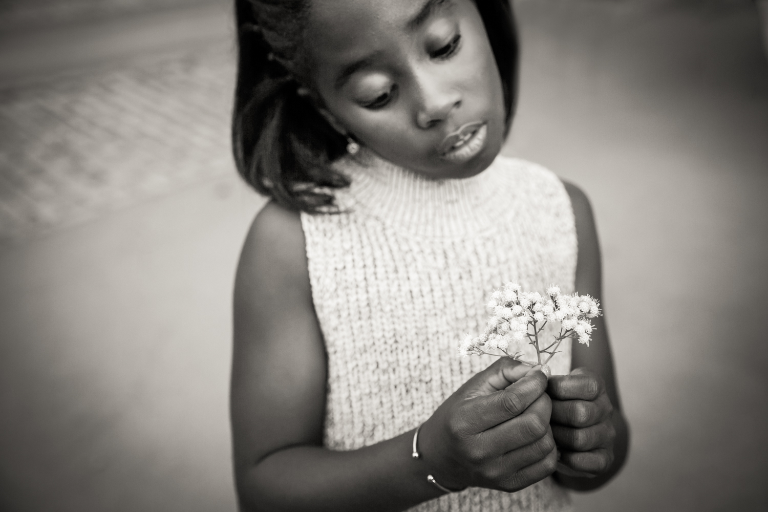 Black and white photo of young girl holding flowers