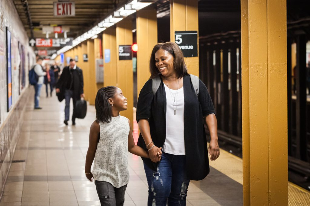 Mother and daughter holding hands and walking on subway platform
