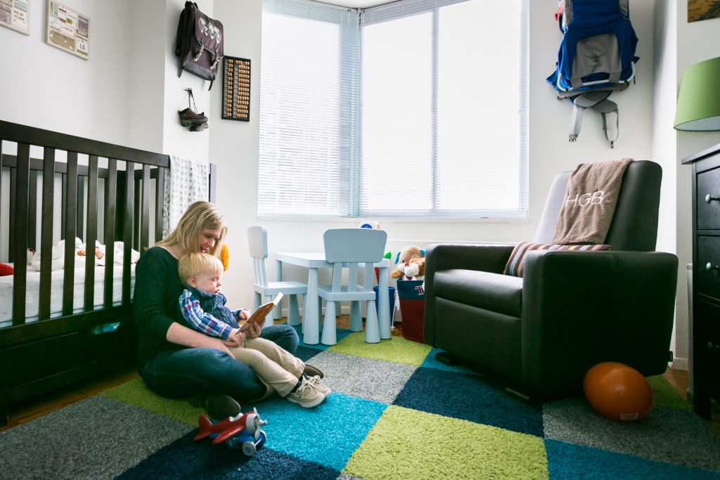 Mother reading to child on the floor of a nursery