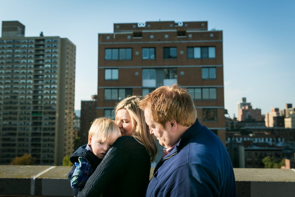 Father and mother holding little blond haired boy with view of NYC skyline in background
