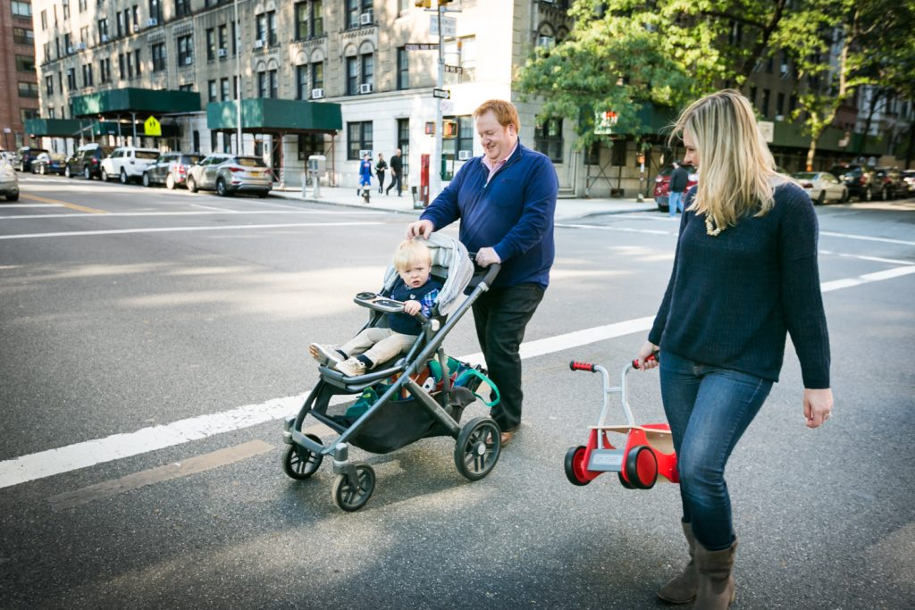 Couple pushing child in stroller across street in NYC