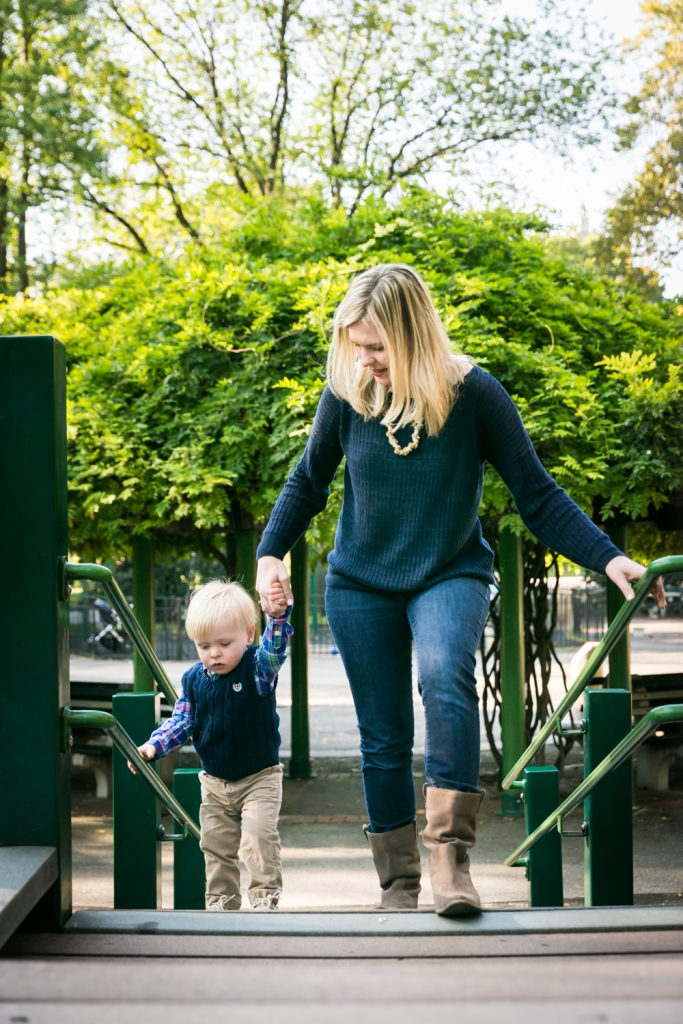 Central Park family photos of mother holding child's hand at playground