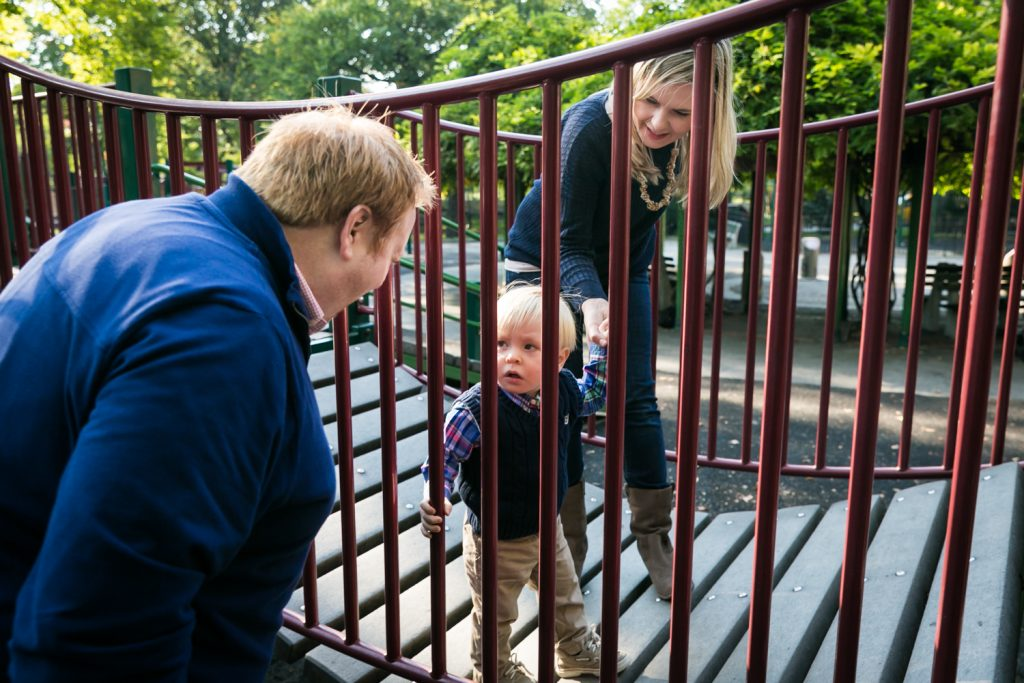 Central Park family photos of parents playing with little boy on playground equipment