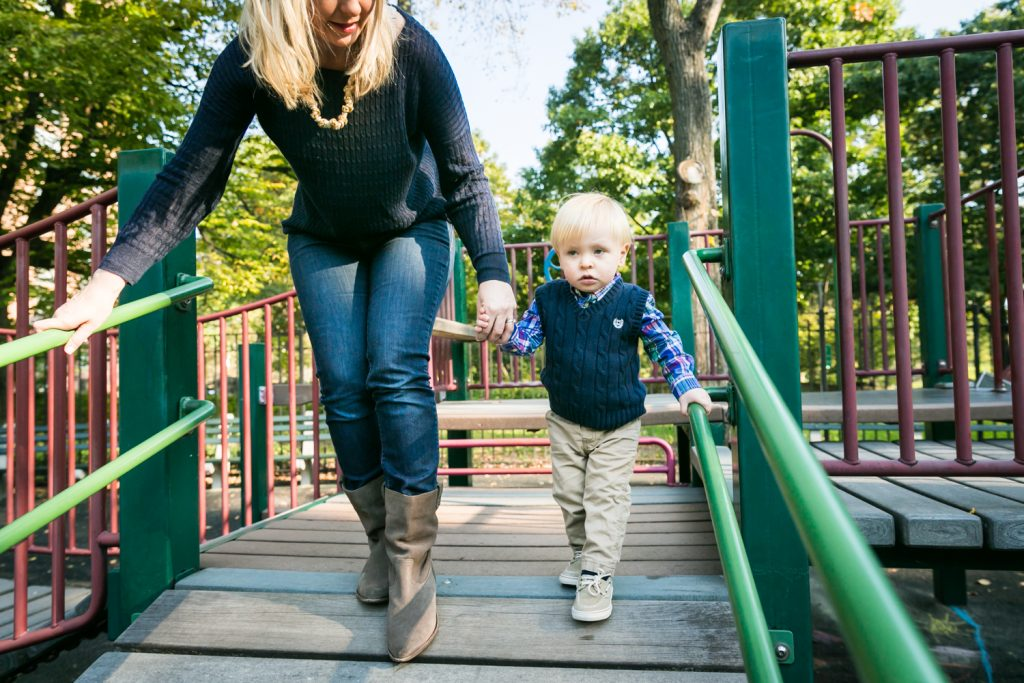 Central Park family photos of mother playing with little boy on playground equipment