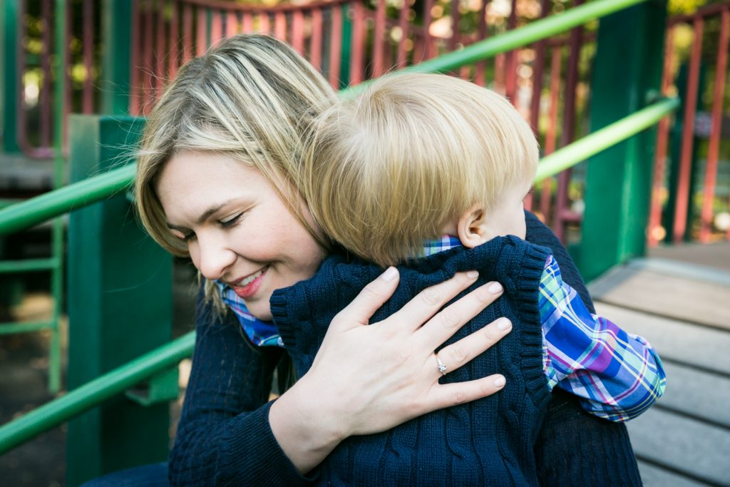Central Park family photos of mother hugging little boy on playground equipment