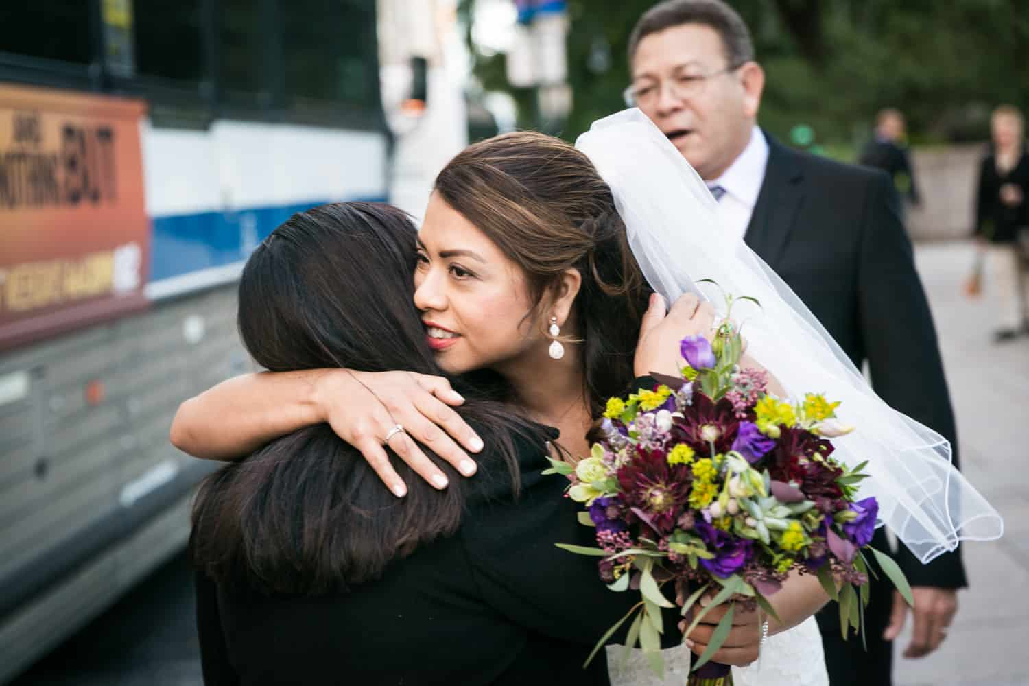 Bride holding bouquet and hugging mother for an article on Central Park wedding planning tips