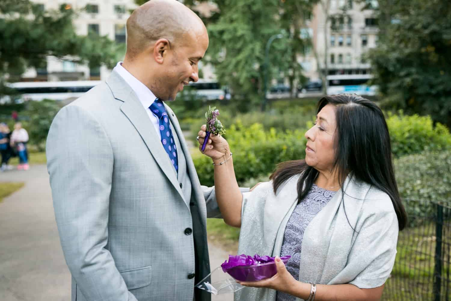 Mother of bride putting boutonniere on groom for an article on Central Park wedding planning tips