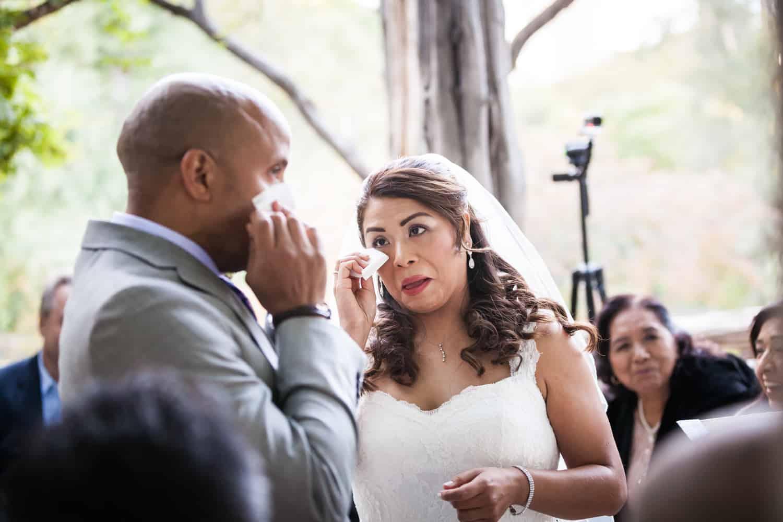 Bride and groom each wiping away tears in Cop Cot wedding