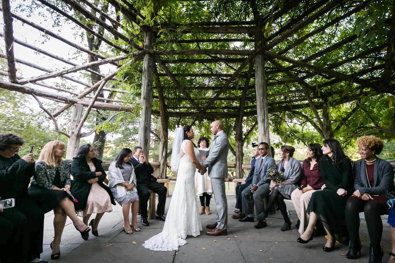 Wide shot of bride and groom holding hands in Cop Cot wedding