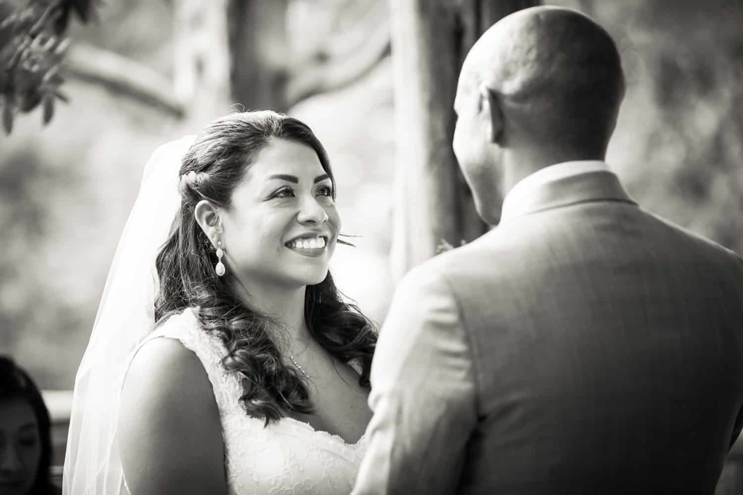 Black and white photo of bride and groom exchanging vows