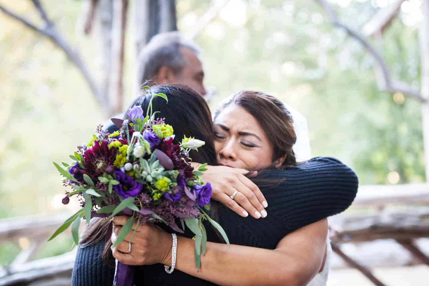 Bride holding bouquet and hugging guest in Cop Cot wedding
