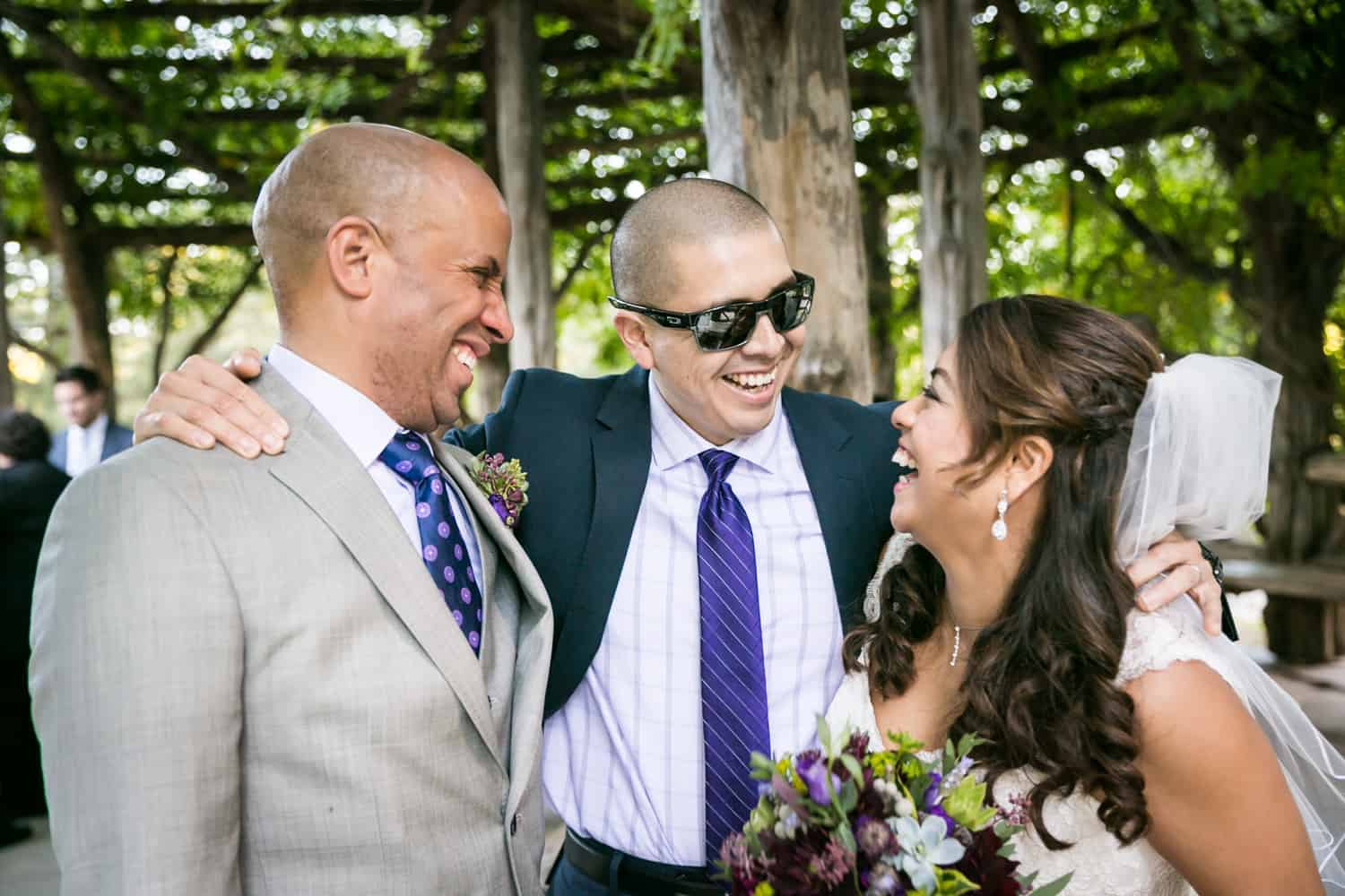 Bride and groom with male guest wearing sunglasses