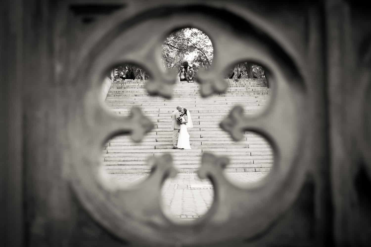 Black and white photo of bride and groom on stairs as views through Central Park fence